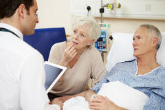 Il dottore With Digital Tablet che parla con coppie dal letto di ospedale Fotografie Stock Libere da Diritti