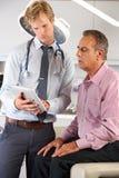 Il dottore Discussing Records With Patient che per mezzo della compressa di Digital Immagini Stock Libere da Diritti