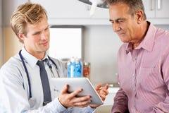 Il dottore Discussing Records With Patient che per mezzo della compressa di Digital Immagine Stock