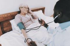 Il dottore Examines Elderly Patient Emicrania paziente fotografia stock