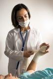 Il dottore Examines un braccio bendato. Verticale Fotografie Stock