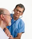 Il dottore Examining Senior Patient con lo stetoscopio immagini stock libere da diritti