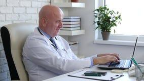 Il dottore felice In Hospital Cabinet facendo uso del collegamento senza fili del computer portatile archivi video
