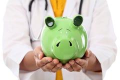 Il dottore femminile Holding Piggy Bank Fotografie Stock