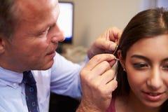 Il dottore Fitting Female Patient con la protesi acustica fotografia stock libera da diritti