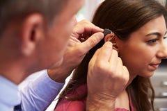 Il dottore Fitting Female Patient con la protesi acustica fotografie stock