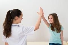 Il dottore Giving High Five alla ragazza Fotografie Stock Libere da Diritti