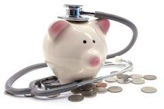 Il dottore Holding Stethoscope alla Banca Piggy Immagini Stock Libere da Diritti