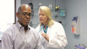 Il dottore Listening To Patient che respira con lo stetoscopio video d archivio