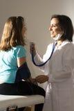 Il dottore Listens il battito cardiaco - verticale Fotografia Stock Libera da Diritti