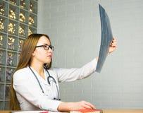 Il dottore Looking della donna alla radiografia dei raggi x nell'ufficio del ` s di medico Fotografia Stock Libera da Diritti