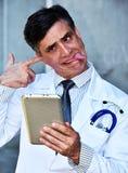 Il dottore maschio insano With Tablet fotografie stock libere da diritti