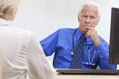 Il dottore maschio maggiore premuroso With Computer immagine stock