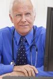 Il dottore maschio maggiore With Stethoscope allo scrittorio fotografia stock libera da diritti