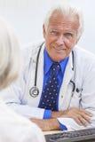 Il dottore maschio senior With Elderly Female Patient immagini stock