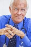 Il dottore maschio senior With Stethoscope allo scrittorio fotografia stock libera da diritti