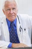 Il dottore maschio senior With Stethoscope allo scrittorio & al computer immagini stock libere da diritti