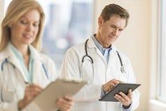 Il dottore maschio Using Digital Tablet all'ospedale immagini stock