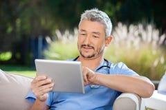 Il dottore maschio Using Digital Tablet mentre sedendosi sopra immagini stock