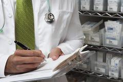 Il dottore maschio Writing On Clipboard Fotografia Stock