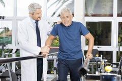 Il dottore Motivating Senior Man da camminare nello studio di forma fisica fotografia stock libera da diritti