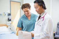 Il dottore And Nurse Looking al rapporto fetale del monitor Fotografia Stock Libera da Diritti