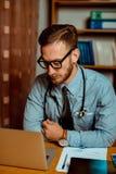 Il dottore Observing X-Ray sul computer portatile fotografie stock libere da diritti