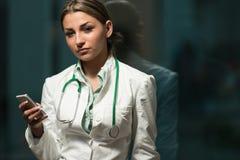 Il dottore occupato Woman Texting On il suo telefono cellulare Immagini Stock