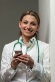 Il dottore occupato Woman Texting On il suo telefono cellulare Fotografie Stock Libere da Diritti