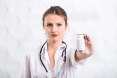 Il dottore Shows Bottle con le droghe Immagine Stock