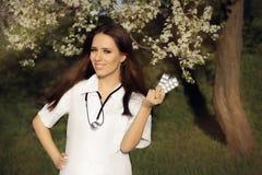 Il dottore Smiling della donna della primavera e pillole della tenuta Fotografia Stock Libera da Diritti