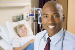 Il dottore Smiling, levantesi in piedi nella stanza di ospedale Immagini Stock