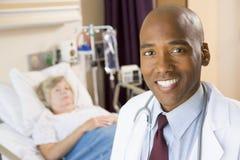 Il dottore Smiling In Patients Room Fotografie Stock Libere da Diritti