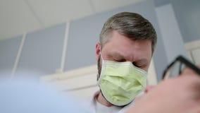 Il dottore Surgeon del dentista in una maschera sta lavorando con il paziente in un ufficio medico stock footage