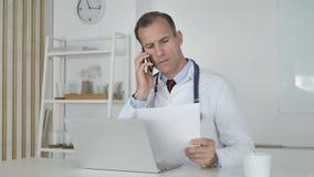 Il dottore Talking sul telefono con paziente, discutendo perizia medica stock footage