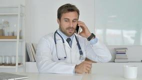 Il dottore Talking sul telefono con paziente, discutendo perizia medica archivi video