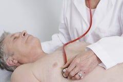 Il dottore Testing Patients Heartbeat che per mezzo dello stetoscopio fotografia stock libera da diritti