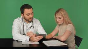 Il dottore Using Digital Tablet che parla con il paziente video d archivio
