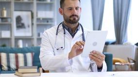 Il dottore Using Tablet per Internet che passa in rassegna stock footage