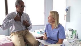Il dottore Writing Up Notes per il paziente maschio Medio Evo video d archivio