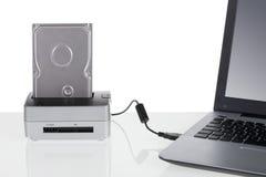 Il drive del hard disk con la stazione di aggancio si è collegato ad un computer portatile Immagine Stock