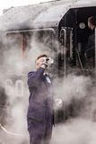 Il driver britannico del treno a vapore beve l'acqua su Nene Valley Railway fotografia stock
