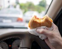 Driver che mangia hamburger nell'automobile Fotografia Stock Libera da Diritti