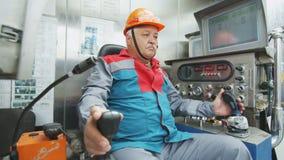 Il driver di mezza età controlla la perforatrice in cabina moderna stock footage