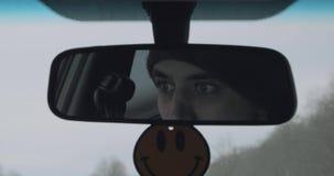 Il driver maschio è riflesso nel retrovisore mentre guida stock footage