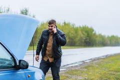 Il driver nervoso chiama al servizio d'assistenza dal telefono Fotografia Stock