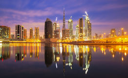 Il DUBAI, gli EMIRATI ARABI UNITI, il 24 febbraio 2016, vista sul centro del Dubai con Burj Khalifa e grattacieli al tramonto, Du Fotografie Stock Libere da Diritti