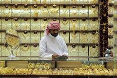 Il Dubai, UAE - 03 marzo, 2017: Venditore dell'oro dentro i gioielli nel souk dell'oro del Dubai immagine stock libera da diritti