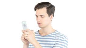Il email di battitura a macchina del giovane, gli sms, massaggio sullo Smart Phone, ha isolato il fondo bianco Fotografia Stock