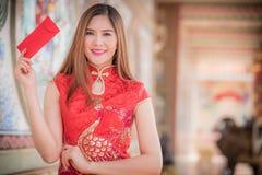 Il envel tradizionale di rosso del cheongsam e della tenuta del vestito cinese dalla donna fotografia stock